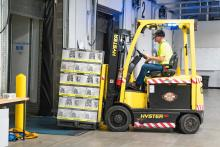 Stock photo of forklift moving boxes